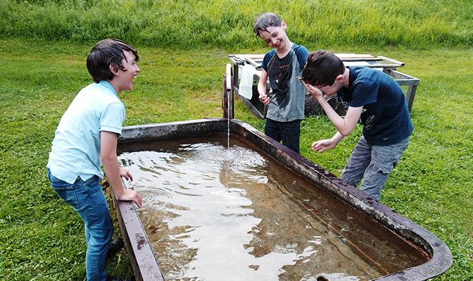 Kinder spielen an Brunnen
