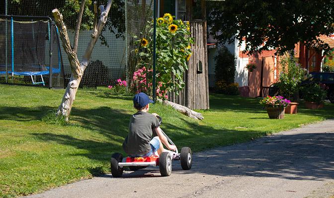 Junge fährt mit Kettcar