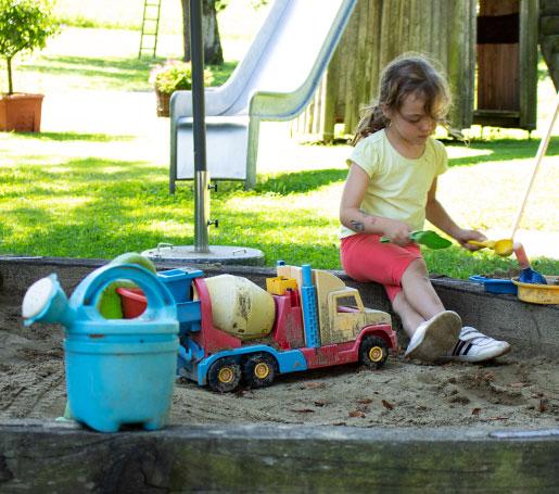 Kind spielt in Sandkasten