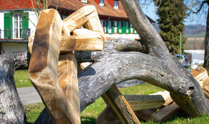 Kunstwerk Holzkette mit Risthof im Hintergrund